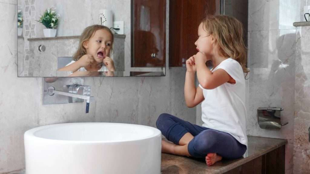 A girl sinking on the counter flossing - Children's Dentistry of Lincoln